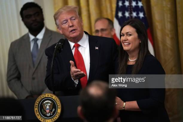 """S President Donald Trump speaks as White House Press Secretary Sarah Sanders listens during an East Room event on """"second chance hiring"""" June 13 2019..."""