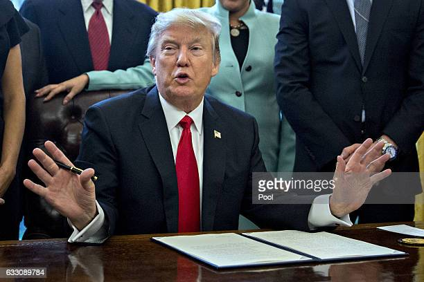 US President Donald Trump speaks before signing an executive order surrounded by small business leaders in the Oval Office of the White House January...