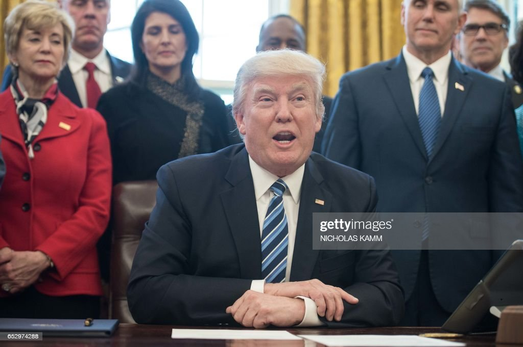 US President Donald Trump speaks before signing an executive order entitled Comprehensive Plan for Reorganizing the Executive Branch in the Oval Office at the White House in Washington, DC, on Marc...