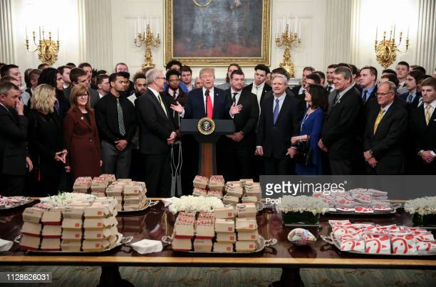 President Donald Trump speaks behind a table full of McDonald's hamburgers, Chick fil-a sandwiches and other fast food as he welcomes the 2018...