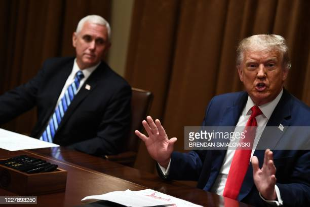 US President Donald Trump speaks next to US Vice President Mike Pence before signing an Executive Order on Hiring American at the White House on...