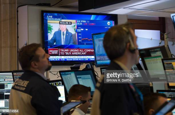 President Donald Trump speaks on television as traders work on the floor at the closing bell of the Dow Industrial Average at the New York Stock...