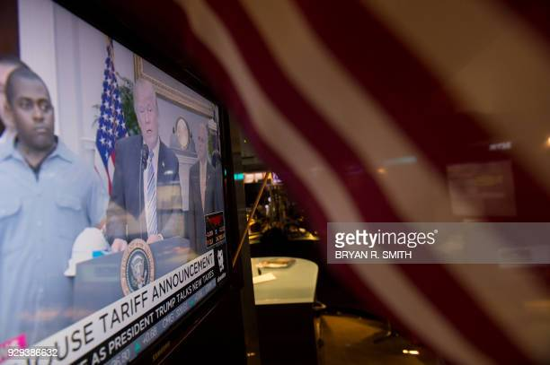 US President Donald Trump speaks on television as traders work on the floor at the closing bell of the Dow Industrial Average at the New York Stock...