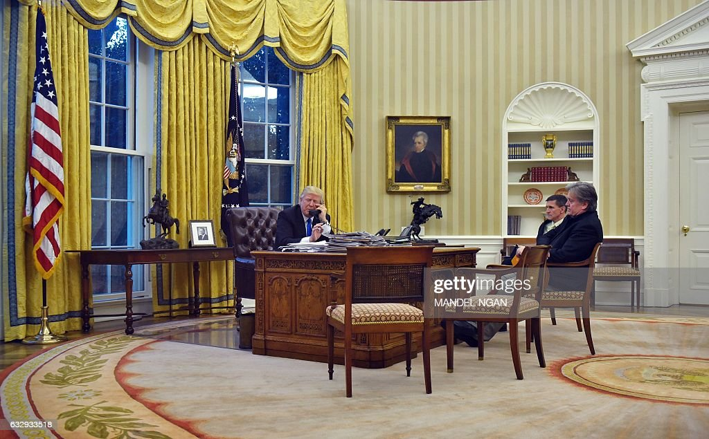 US President Donald Trump speaks on the phone with Australia's Prime Minister Malcolm Turnbull, alongside Chief Strategist Steve Bannon (R) and National Security Advisor Michael Flynn, from the Oval Office of the White House on January 28, 2017, in Washington, DC. / AFP / Mandel Ngan