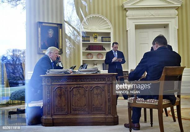 US President Donald Trump speaks on the phone with Germany's Chancellor Angela Merkel from the Oval Office of the White House on January 28 2017 in...