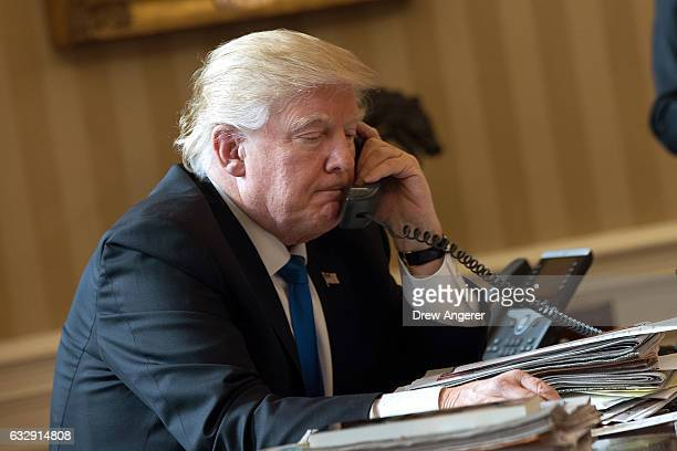 President Donald Trump speaks on the phone with Russian President Vladimir Putin in the Oval Office of the White House January 28 2017 in Washington...