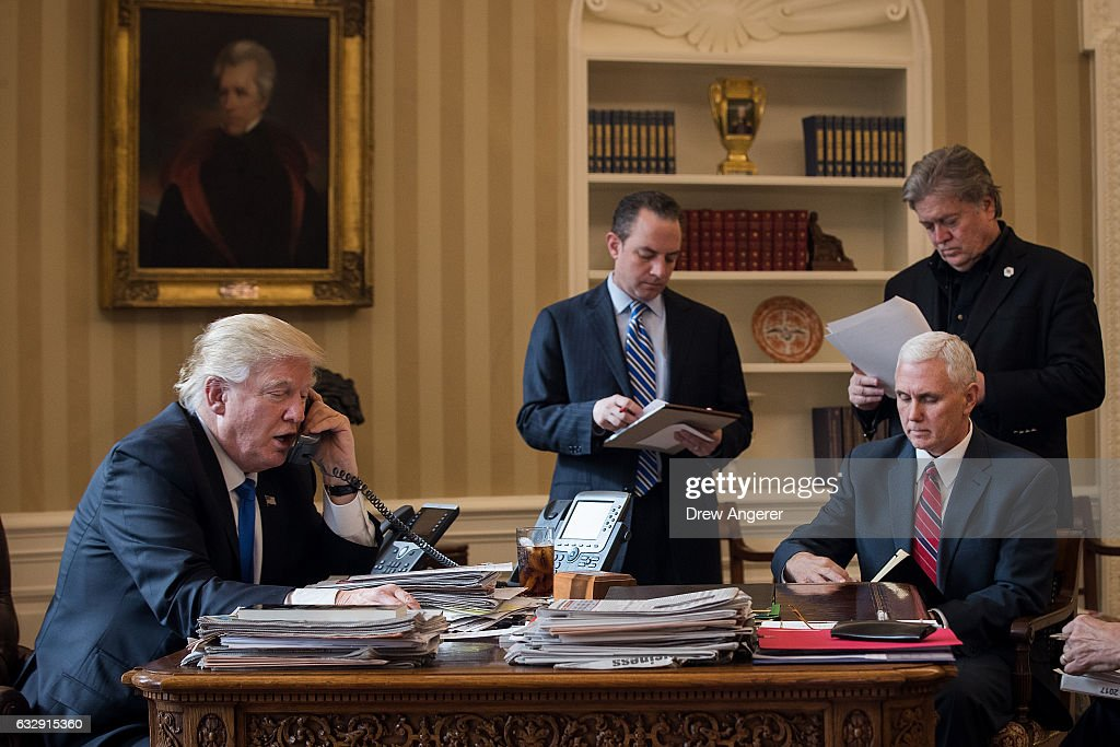 President Donald Trump speaks on the phone with Russian President Vladimir Putin in the Oval Office of the White House, January 28, 2017 in Washington, DC. Also pictured, from left, White House Chief of Staff Reince Priebus, Vice President Mike Pence, and White House Chief Strategist Steve Bannon. On Saturday, President Trump is making several phone calls with world leaders from Japan, Germany, Russia, France and Australia.