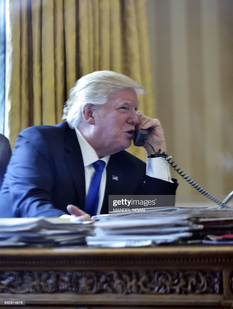 US President Donald Trump speaks on the phone with Russia's President Vladimir Putin from the Oval Office of the White House on January 28, 2017, in Washington, DC.