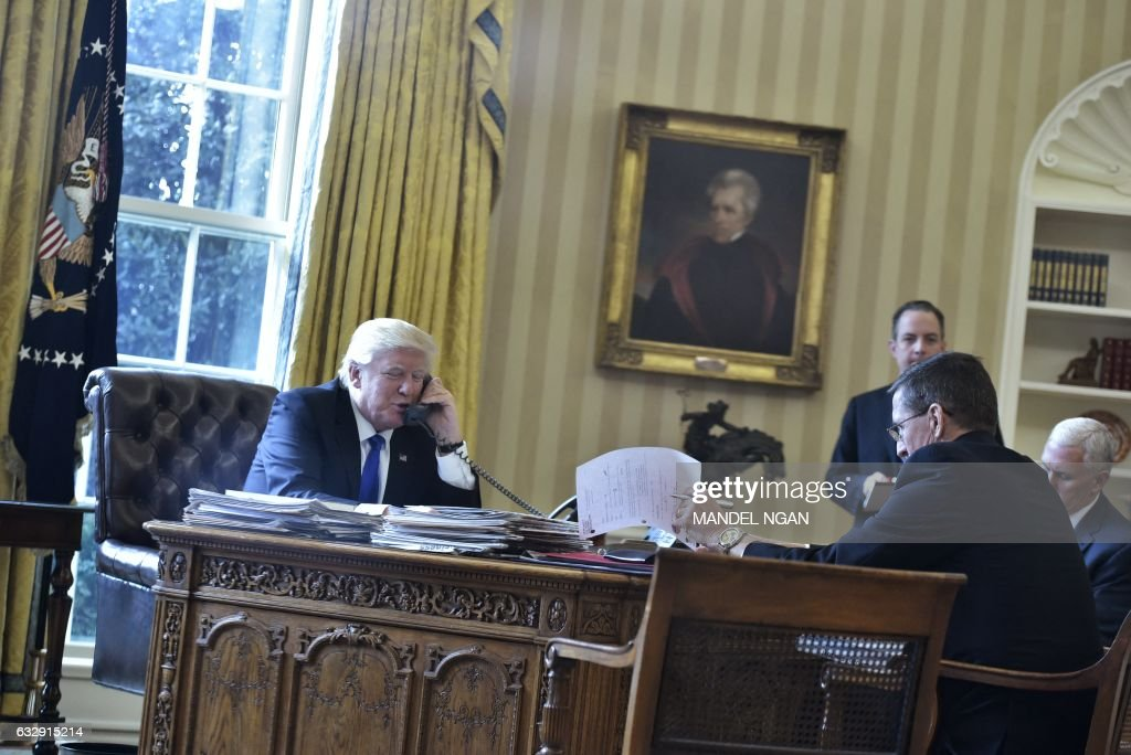 US President Donald Trump speaks on the phone with Russia's President Vladimir Putin from the Oval Office of the White House on January 28, 2017, in Washington, DC. White House Chief of Staff Reince Priebus, National Security Advisor Michael Flynn and Vice President Mike Pence. / AFP / MANDEL