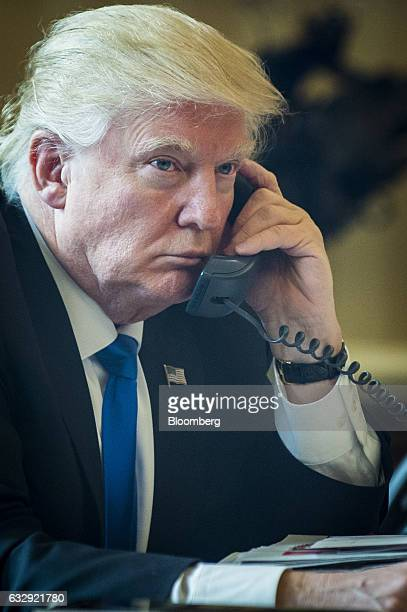 US President Donald Trump speaks on the phone with Vladimir Putin Russia's president during the first official phone talks in the Oval Office of the...