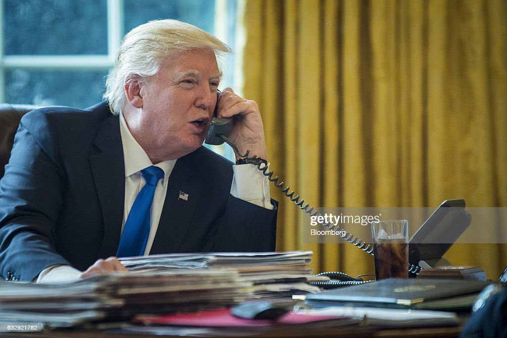 U.S. President Donald Trump speaks on the phone with Vladimir Putin, Russia's president, during the first official phone talks in the Oval Office of the White House in Washington, D.C., U.S., on Saturday, Jan. 28, 2017. Putin and Trump exchanged views on Russia-U.S. relations as Republicans in the U.S. Senate intensify calls to keep sanctions on Russia in place. Photographer: Pete Marovich/Pool via Bloomberg