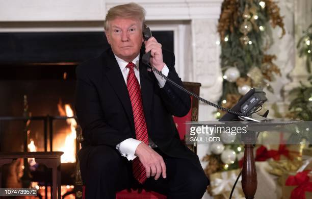 US President Donald Trump speaks on the telephone as he answers calls from people calling into the NORAD Santa tracker phone line in the State Dining...