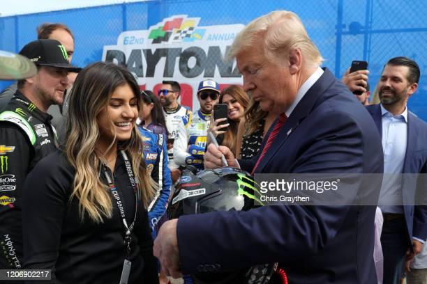 S President Donald Trump speaks signs the helmet of Hailie Deegan prior to the NASCAR Cup Series 62nd Annual Daytona 500 at Daytona International...