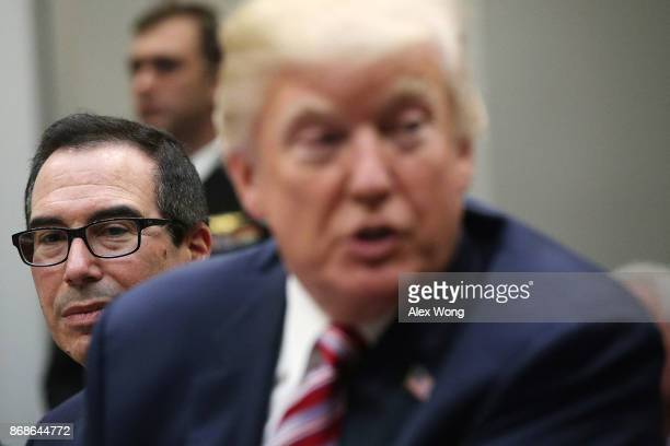 S President Donald Trump speaks to business leaders as Secretary of the Treasury Steven Mnuchin looks on during a Roosevelt Room event October 31...
