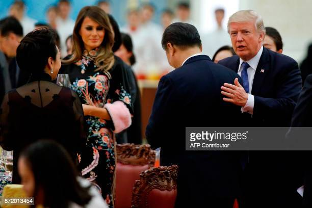 US President Donald Trump speaks to China's President Xi Jinping beside US First Lady Melania Trump and Xi's wife Peng Liyuan during a state dinner...