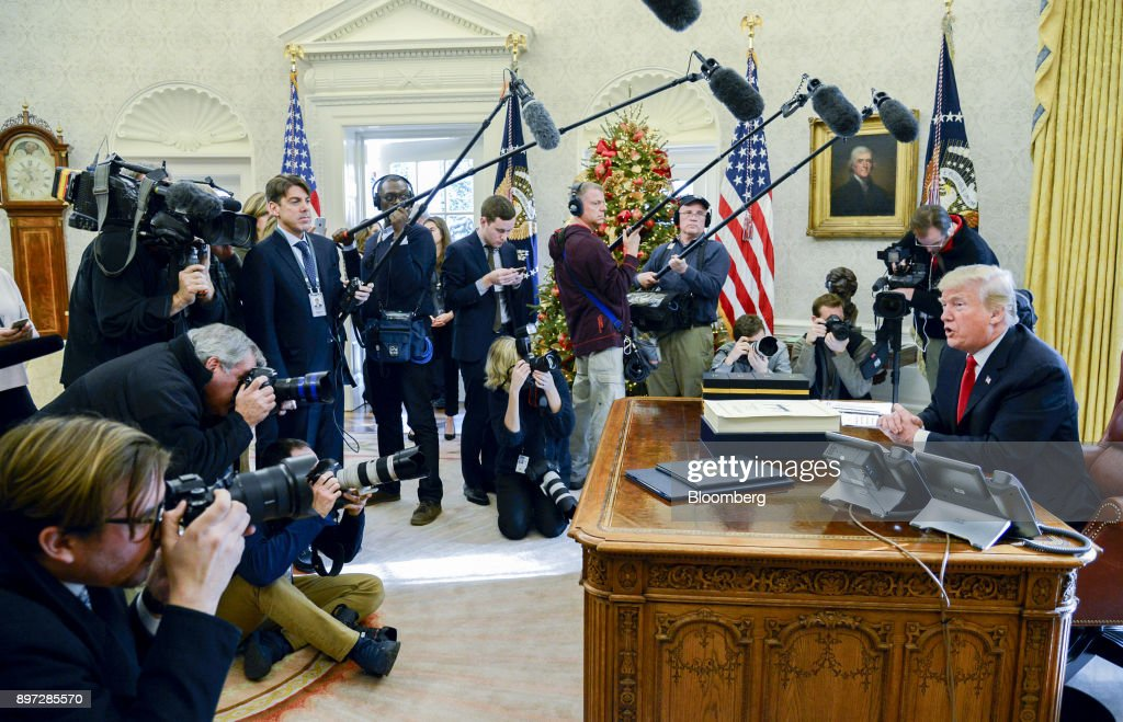 U.S. President Donald Trump speaks to members of the media after signing a tax-overhaul bill into law in the Oval Office of the White House in Washington, D.C., U.S., on Friday, Dec. 22, 2017. This week House Republicans passed the most extensive rewrite of the U.S. tax code in more than 30 years, hours after the Senate passed the legislation, handing Trump his first major legislative victory providing a permanent tax cut for corporations and shorter-term relief for individuals. Photographer: Mike Theiler/Pool via Bloomberg