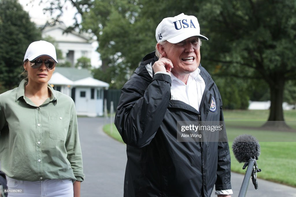 U.S. President Donald Trump (R) speaks to members of the media as first lady Melania Trump (L) looks on after they return to the White House from Florida September 14, 2017 in Washington, DC. President Trump has returned from viewing the relief efforts in the wake of Hurricane Irma.