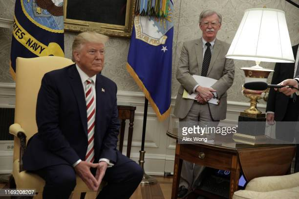 S President Donald Trump speaks to members of the media as National Security Adviser John Bolton listens during a meeting with President of Romania...