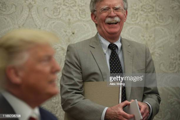 President Donald Trump speaks to members of the media as National Security Adviser John Bolton listens during a meeting with President of Romania...