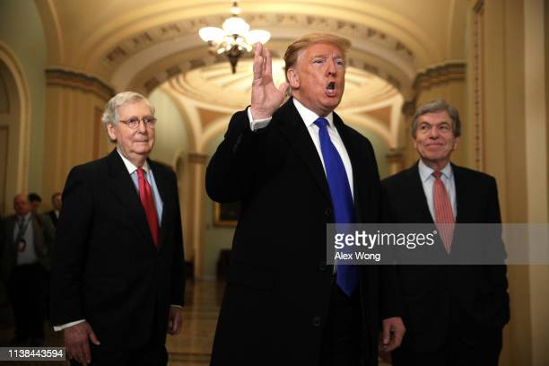S President Donald Trump speaks to members of the media as Senate Majority Leader Sen Mitch McConnell and Sen Roy Blunt look on after he arrived at a...