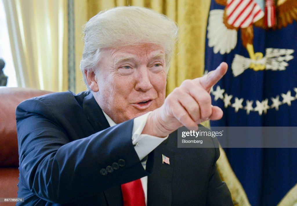 U.S. President Donald Trump speaks to members of the media before signing a tax-overhaul bill into law in the Oval Office of the White House in Washington, D.C., U.S., on Friday, Dec. 22, 2017. This week House Republicans passed the most extensive rewrite of the U.S. tax code in more than 30 years, hours after the Senate passed the legislation, handing Trump his first major legislative victory providing a permanent tax cut for corporations and shorter-term relief for individuals. Photographer: Mike Theiler/Pool via Bloomberg