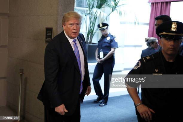 US President Donald Trump speaks to members of the media while walking to a House Republican conference meeting on immigration legislation at the US...