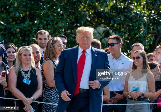 President Donald Trump speaks to members of the press before departing from the White House on the south lawn before he boards Marine One on August...