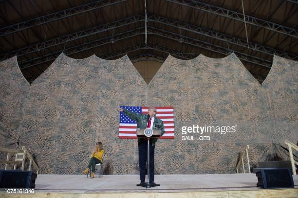 US President Donald Trump speaks to members of the US military as First Lady Melania Trump looks on during an unannounced trip to Al Asad Air Base in...