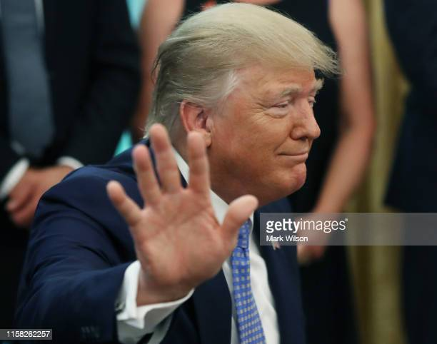 President Donald Trump speaks to reporters about Iran and Mexico after signing an executive order establishing a White House Council on eliminating...