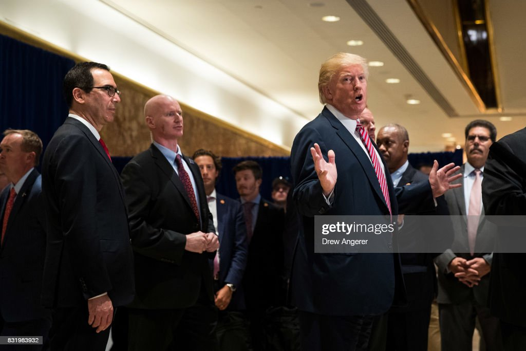 US President Donald Trump speaks to reporters on his way out of the lobby following a meeting on infrastructure at Trump Tower, August 15, 2017 in New York City. He fielded questions from reporters about his comments on the events in Charlottesville, Virginia and white supremacists.