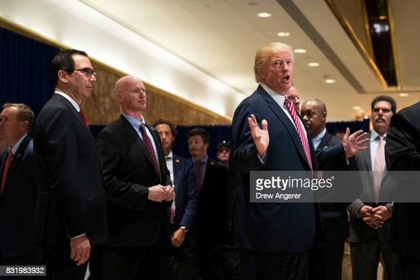 President Donald Trump speaks to reporters on his way out of the lobby following a meeting on infrastructure at Trump Tower August 15 2017 in New...