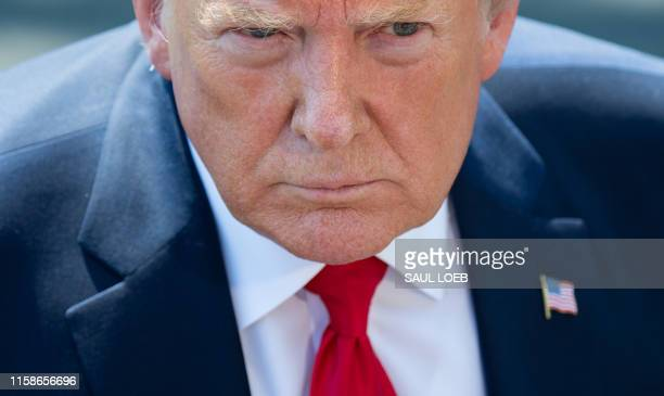 US President Donald Trump speaks to the media after arriving on the South Lawn of the White House in Washington DC July 30 following a trip to the...