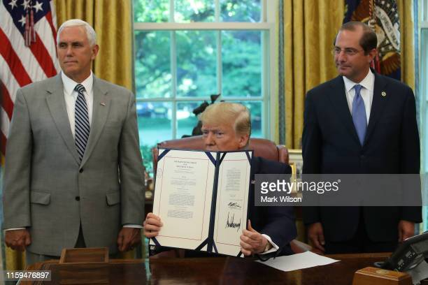 President Donald Trump speaks to the media after signing a bill for border funding legislation while flanked by Vice President Mike Pence and Health...