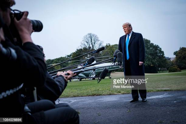 President Donald Trump speaks to the media as he prepares to board Marine One on the South Lawn of the White House on October 26 2018 in Washington...
