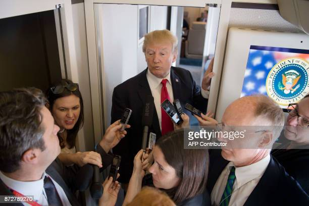 US President Donald Trump speaks to the media onboard Air Force One after departing from Danang on his way to Hanoi on November 11 2017 Trump...
