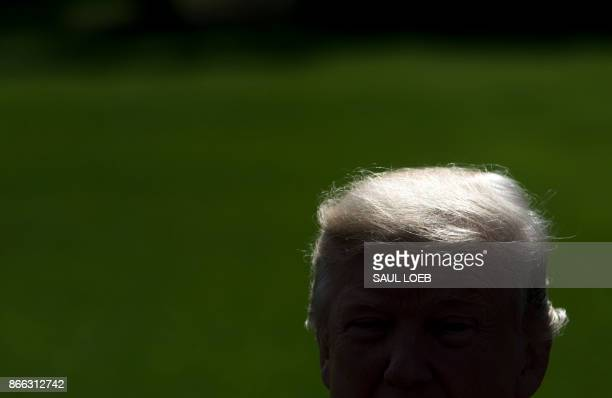 US President Donald Trump speaks to the media prior to departing on Marine One from the South Lawn of the White House in Washington DC October 25 as...