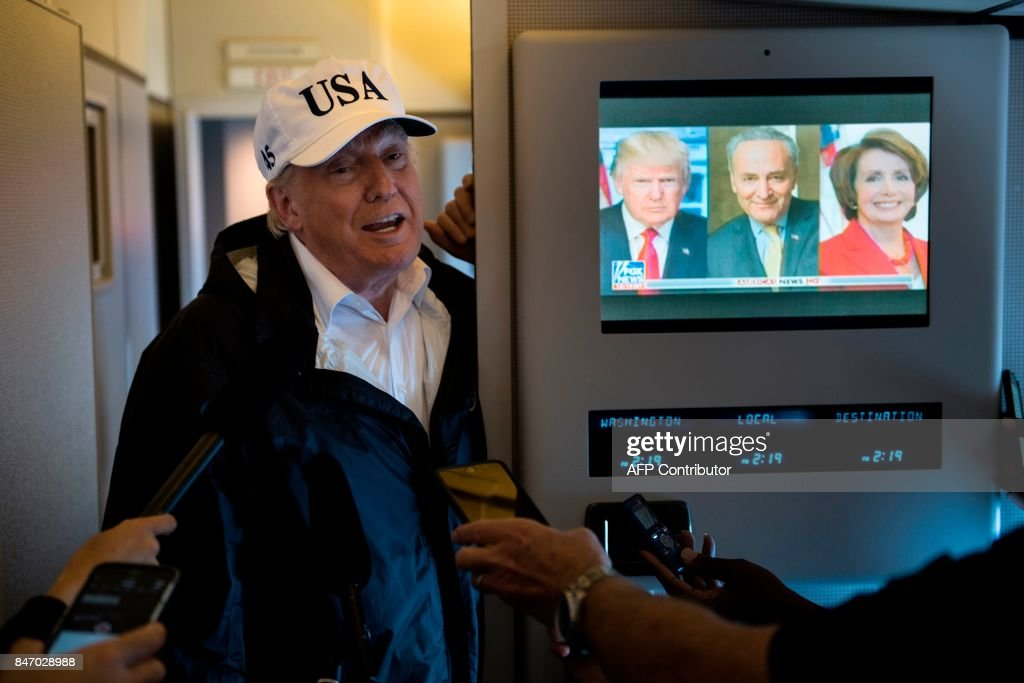 US President Donald Trump speaks to the press onboard Air Force One while flying back to Andrews Air Force Base September 14, 2017 over, Florida. / AFP PHOTO / Brendan Smialowski