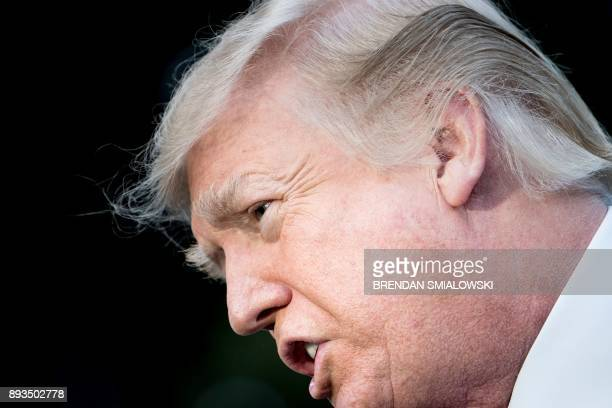 US President Donald Trump speaks to the press while walking to Marine One on the South Lawn of the White House December 15 2017 in Washington DC /...