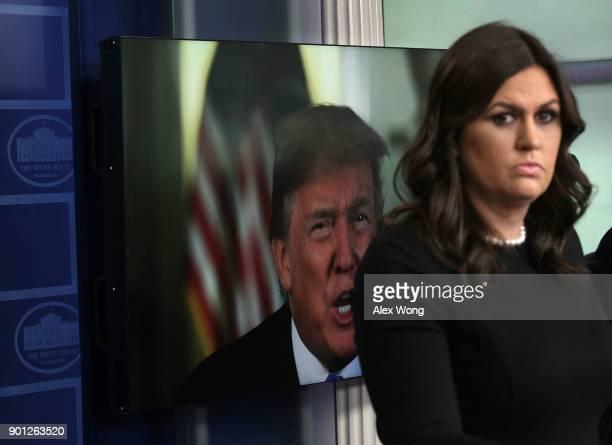 President Donald Trump speaks via a video as White House Press Secretary Sarah Sanders listens during a daily news briefing at the James Brady Press...