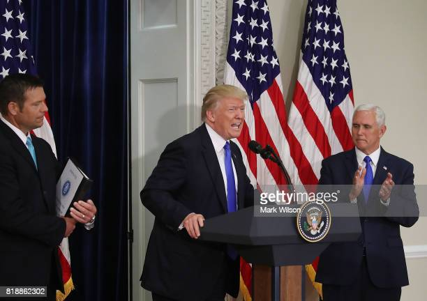 S President Donald Trump speaks while flanked by Kansas Secretary of State Kris Kobach and US Vice President Mike Pence during the first meeting of...