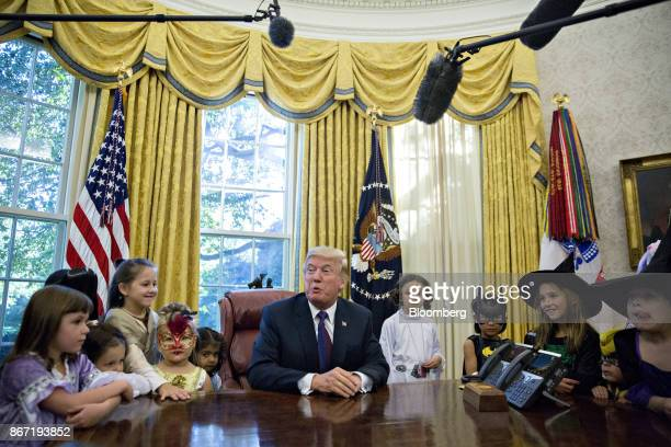 US President Donald Trump speaks while meeting with children of the White House press corps dressed in Halloween costumes at the Oval Office in...