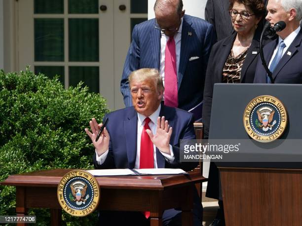 US President Donald Trump speaks while signing the Paycheck Protection Program Flexibility Act of 2020 as he holds a press conference on the economy...