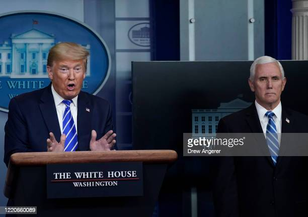 President Donald Trump speaks while Vice President Mike Pence listens during the daily briefing of the coronavirus task force at the White House on...
