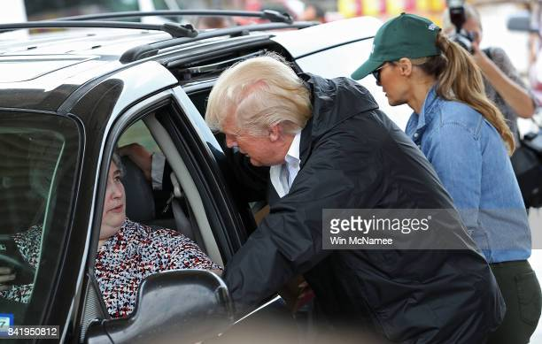 S President Donald Trump speaks with a resident of the Pearland Texas area as first lady Melania Trump loads emergency supplies into the back of a...