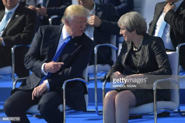 US President Donald Trump speaks with Britain's Prime Minister Theresa May as they attend the NATO summit ceremony at the NATO headquarters in...