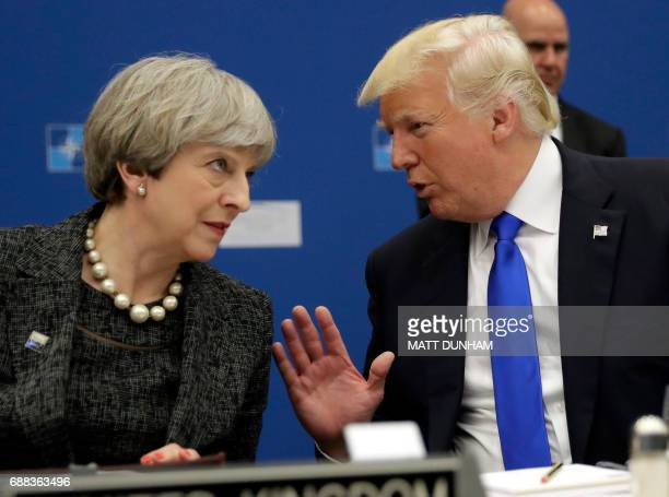 US President Donald Trump speaks with British Prime Minister Theresa May during in a working dinner meeting at the NATO summit at the NATO...