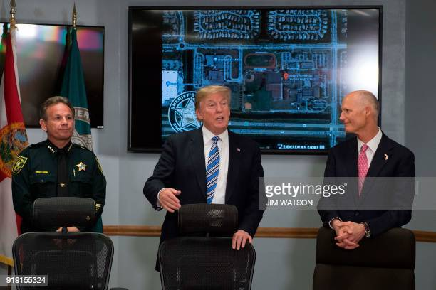 US President Donald Trump speaks with Broward County Sheriff Scott Israel and Florida Governor Rick Scott while visiting first responders at Broward...