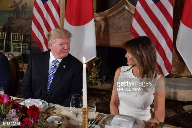 US President Donald Trump speaks with First Lady Melania Trump during a dinner with Japan's Prime Minister Shinzo Abe and his wife Akie Abe at...