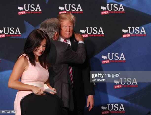 S President Donald Trump speaks with Maximo Alvarez next to Irina Vilatino during a roundtable discussion about the Republican $15 trillion tax cut...