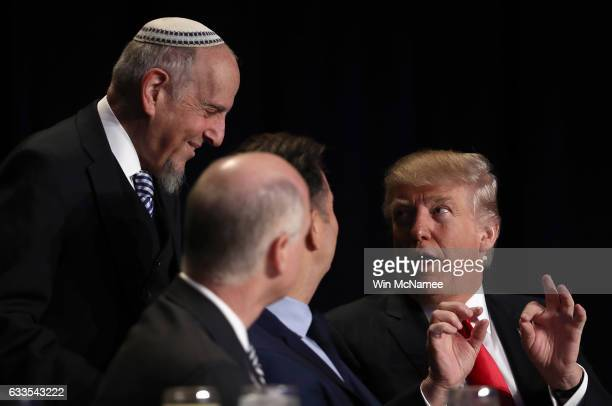 US President Donald Trump speaks with members of the head table at the National Prayer Breakfast February 2 2017 in Washington DC Every US president...